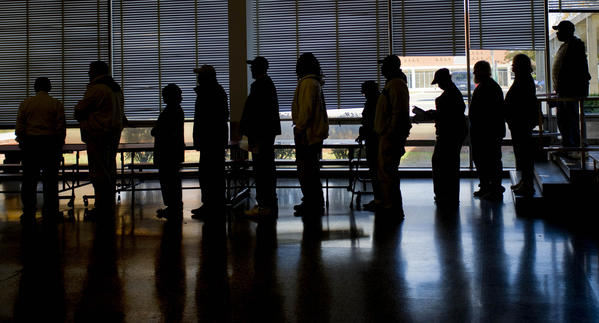 Voters are silhouetted as they wait to vote at Woodlawn High School.