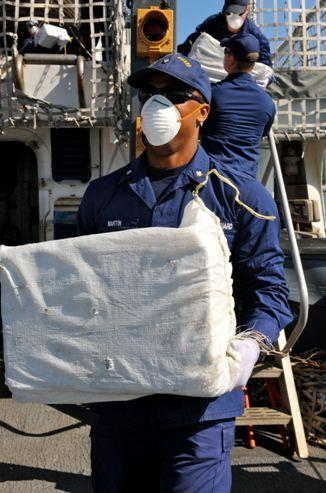 Coast Guard Petty Petty Officer 3rd Class Joshua Martin, a crewmember aboard the Coast Guard Cutter Bear carries a bale of cocaine off the deck during an offload of more than 1,851 pounds of cocaine, with a wholesale value of more than $22 million, at Coast Guard Base Miami Beach. U.S. Coast Guard Law Enforcement Detachment onboard the HNLMS Van Amstel, of the Royal Netherlands Navy, assisted in recovering 42 bales of cocaine during a counter drug patrol in the Caribbean Sea