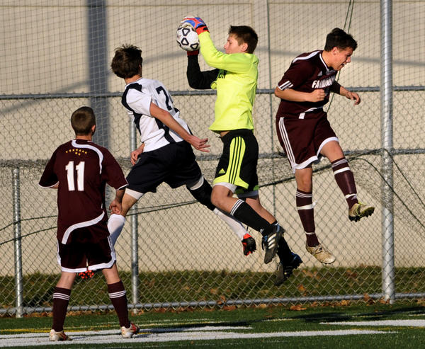 Farmington's goalkeeper Jeffrey Crook stops a shot on goal by Avon's Jackson Davey (7) in the second half in the Class L championship game Friday at Falcon Field. At right is Farmington's Justin Rappaport (10). Farmington beat Avon, 5-0 for the title.