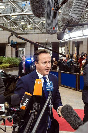 British Prime Minister David Cameron talks to reporters Friday at summit of European Union leaders in Brussels.