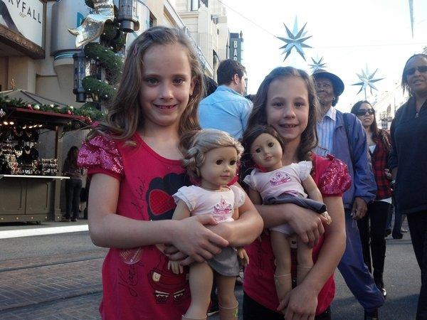 Kaitlyn and Kristin Welch hold their new American Girl dolls, an early Christmas and birthday gift from their mother and grandmother, at the Grove shopping center.
