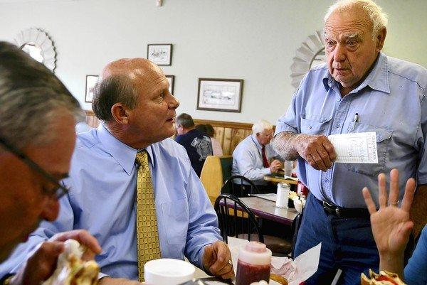 "Sheriff Terry Johnson, center, talks with resident Charles Smith, right, at a local eatery in 2009. ""We don't have enough work in this country to support people who are here legally. Why should we be keeping illegal immigrants?"" Smith says."