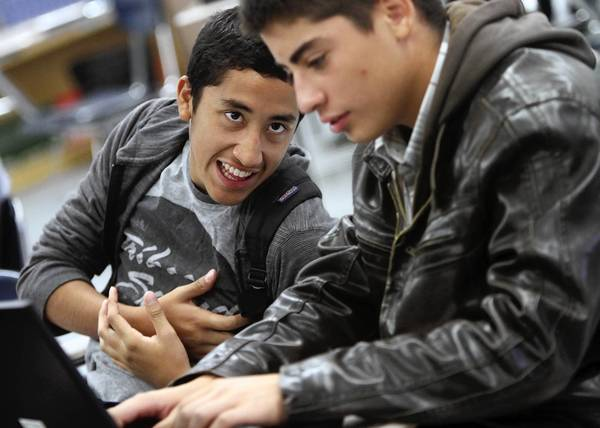 Brian Caballero, left, encourages Jimmy Fuentes, while he emails his counselor during a College Summit session at Sylmar High School.