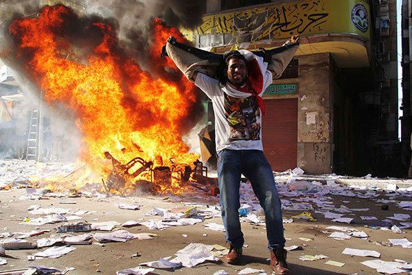 "A protester cheers as items ransacked from an office of the Muslim Brotherhood's Freedom and Justice Party burn in Alexandria November 23, 2012. Egyptian President Mohamed Mursi's decree that put his decisions above legal challenge until a new parliament was elected caused fury amongst his opponents on Friday who accused him of being the new Hosni Mubarak and hijacking the revolution. Police fired tear gas in a street leading to Cairo's Tahrir Square, heart of the 2011 anti-Mubarak uprising, where thousands demanded Mursi quit and accused him of launching a ""coup"". There were violent protests in Alexandria, Port Said and Suez."