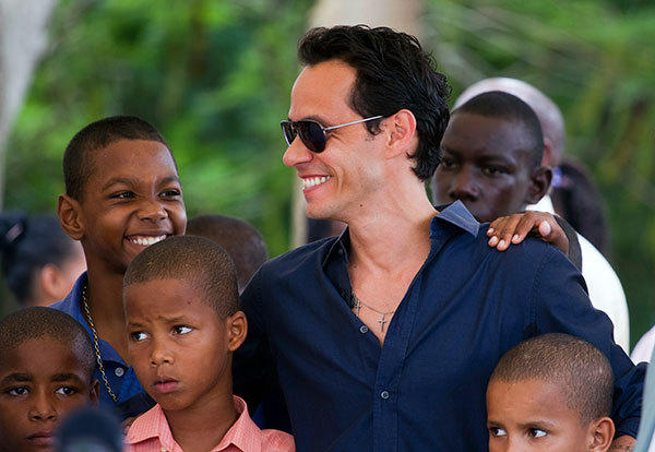 Puerto Rican singer Marc Anthony poses with children during the opening ceremony of the construction of the Orphanage Children of Christ  in La Romana, Dominican Republic on November 23, 2012.