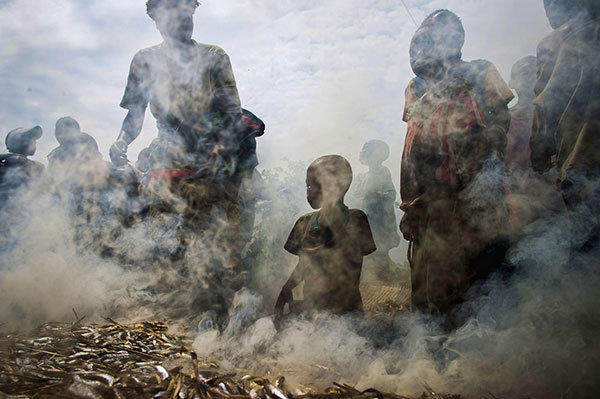 A group of displaced Congolese gather around fish being smoked in Mugunga in the east of the Democratic Republic of the Congo on November 23, 2012. Fresh fighting yesterday between M23 rebels and government troops in Sake caused tens of thousands to flee the area yesterday, taking refuge in Mugunga. The M23 rebels on Tuesday captured Goma, and a day later the nearby town of Sake, displacing tens of thousands of people and raising concerns of a looming humanitarian catastrophe in the area, which has a long history of unrest.