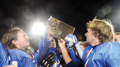 Berlin players hold up the championship trophy after winning the District 5 Class A football title on Friday night.