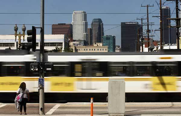 A Metro Blue Line train zips past a pedestrian near the intersection of Washington Boulevard and Flower Street.