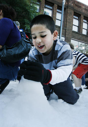 Tristan Castro, 6, of Sylmar, makes a snowman in 20-tons of snow on Holly Street sponsored by the Old Pasadena Management District in Pasadena on Friday, November 23, 2012.