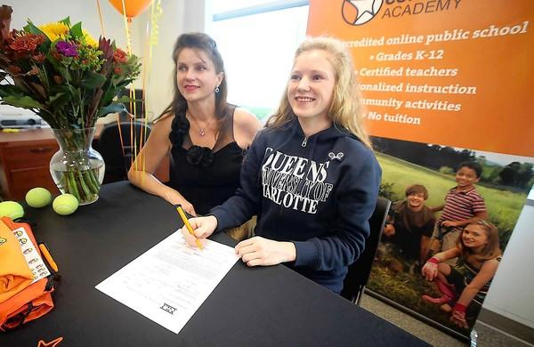 Olivia Laws, right, with her mom Mila Sukhaya on her side, signs a letter of intent for Queens University of Charlotte in North Carolina. Laws won a $13,000 scholarship to the university.