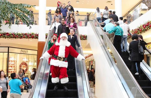 Santa Claus takesthe escalator to his post in Santa's Village to hear what kids want for Christmas during South Coast Plaza's Black Friday shopping action.