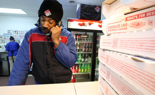 Andre Cobbs takes an order over the phone Friday night as he worked his shift at Domino's Pizza in Aberdeen.