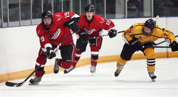 Zach Kraft of the Aberdeen Wings, left, pushes the puck up ice ahead of teammate Heinz Koster (12) and Drew Anderson of the Austin Bruins, right, during the first period of Friday night's game at the Odde Ice Center.