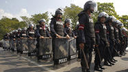 Riot police stand guard around the government house in preparation for anti-government protests in Bangkok