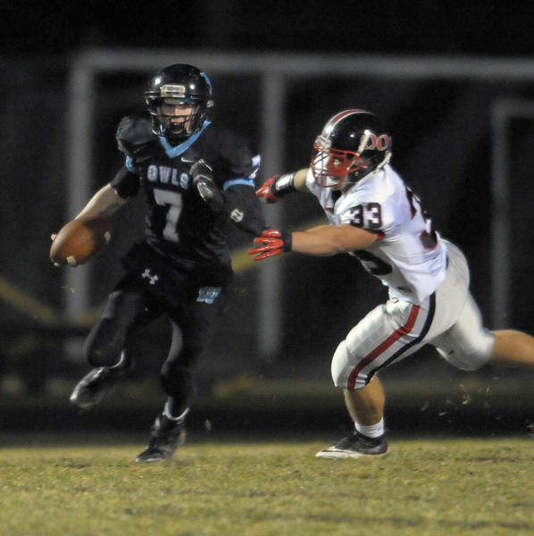 Westminster quarterback Deryk Kern, left, escapes Quince Orchard's Carlo St. Regis in the first half.