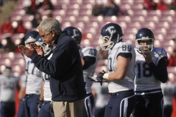 Head coach Paul Pasqualoni encourages his players during warm-ups before the Huskies take on Louisville at Papa John's Stadium Saturday.