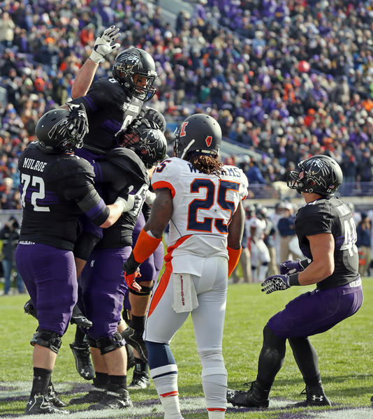 Tony Jones of Northwestern (6) is hoisted by teammates after making a touchdown reception in the second quarter against Illinois at Ryan Field Saturday.