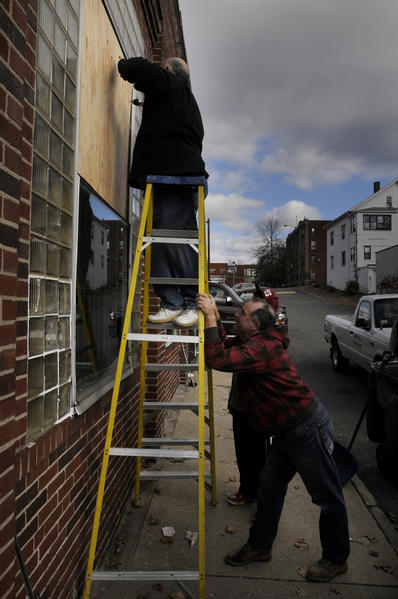 Rene Young, owner of AA Automotive, located on Winter Street directly behind the building that exploded, boards up windows in his building that were blown out in the explosion. Ron Hood, of Springfield, holds the ladder.