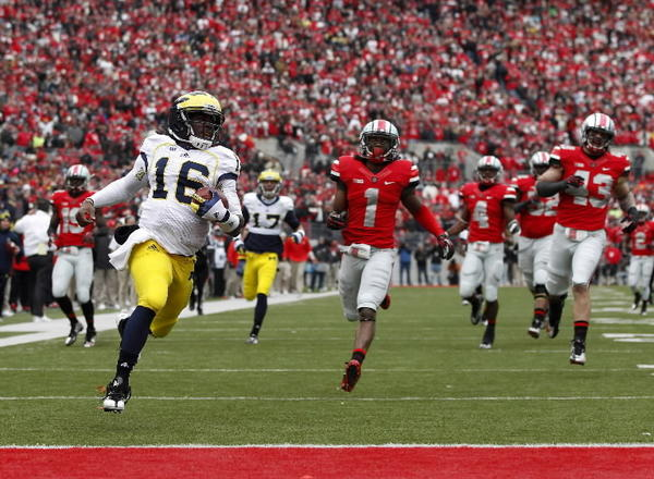 Michigan Wolverines quarterback Denard Robinson (16) scores a touchdown as Ohio State Buckeyes defenders Bradley Roby (1) and Nathan Williams (43) look on during the first half of their NCAA college football game at Ohio Stadium in Columbus, Ohio, November 24, 2012. REUTERS/Matt Sullivan