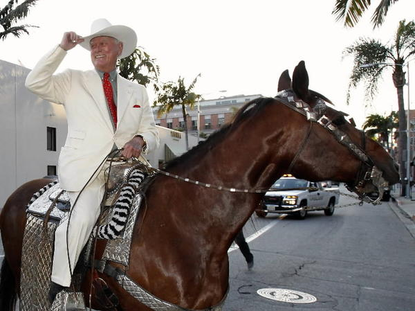 Larry Hagman in high PR mode arriving on horseback in Beverly Hills for a collection of his artwork.