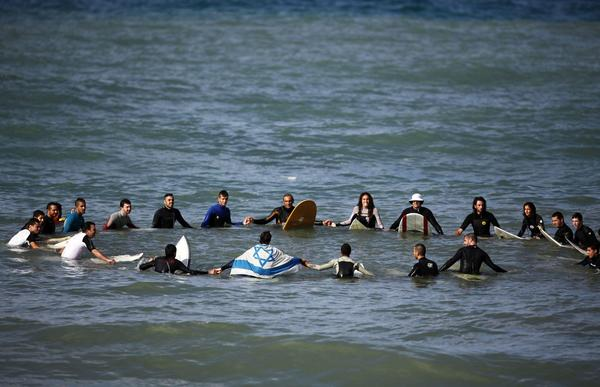 Israeli surfers gather in a circle off shore in the Mediterranean near the city of Ashkelon November 24, 2012. About 30 local surfers gathered in the water to mark the end of a week of fierce fighting between Israeli forces and Hamas militants in the nearby Gaza strip.