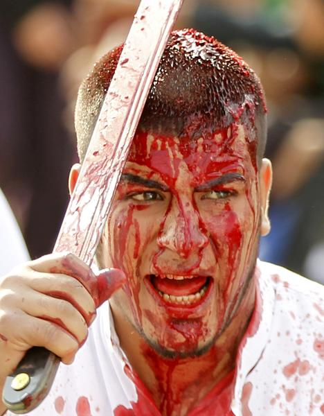 An Iraqi Shi'ite Muslim man gashes his forehead with a sword during a ceremony marking Ashura in Baghdad's Sadr City. Shi'ite Muslims beat themselves during Ashura with steel-tipped flails or slash their bodies with knives to mark the death anniversary of Imam Hussein, a grandson of the Prophet Mohammad, who was killed in the 7th century battle of Kerbala.