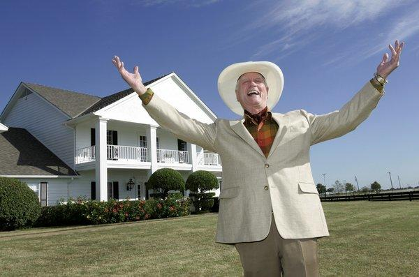 "Larry Hagman poses in front of the Southfork Ranch mansion in Parker, Texas, made famous in the television show ""Dallas."""