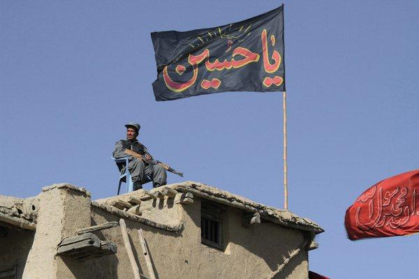 An Afghan policeman sits guard on a rooftop overlooking an Ashura procession in Kabul, Afghanistan.
