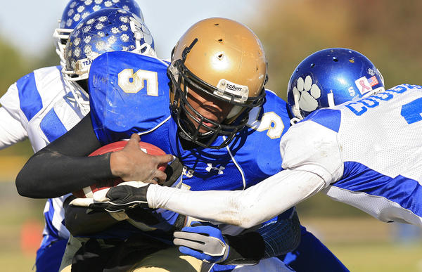Jamal Wells of Smithfield carries the ball and braces for a tackle by Darien Grant of Courtland during the forth quarter of the Region I Division 4 football championship game at Smithfield High School on Saturday, November 24, 2012.