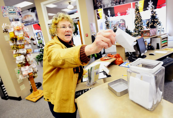 Holiday shopper Anna Maysak of Hagerstown places her entry in a glass jar Saturday afternoon for a chance at the Small Business Saturday $100 drawing.