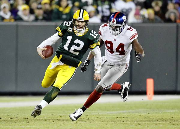 Green Bay Packers quarterback Aaron Rodgers (12) is chased by New York Giants outside linebacker Mathias Kiwanuka (94) during the second half in the 2011 NFC divisional playoff game at Lambeau Field.