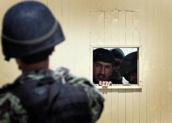 Afghan soldiers look through the security hole of one of the gates at the Kabul airport after a deadly shooting rampage in April 2011.
