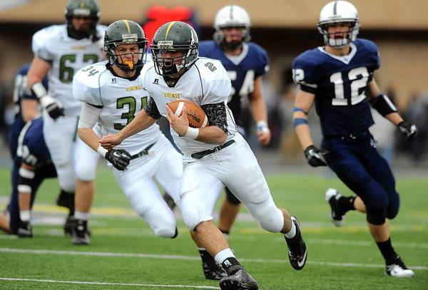 Central Catholic's Colin McDermott (center) runs through Abington Heights' defense for a large gain during their PIAA 3A playoff game Saturday afternoon.