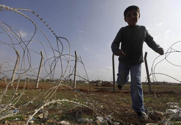 "A Syrian boy from the northern Syrian town of Ras al-Ain runs from a Turkish soldier as he succeeds in passing the border fence into the Turkish border town of Ceylanpinar, Sanliurfa province, November 24, 2012. Syria on Friday condemned Turkey's request for NATO to deploy Patriot defence missiles near their common border, calling it ""provocative"", after a spate of clashes there that has raised fear of the Syrian civil war embroiling the wider region."