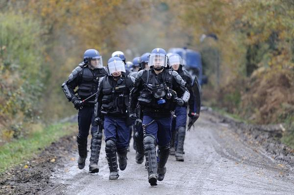 French riot police march on November 24, 2012 as they seek to evict squatters from protected swampland where Prime Minister Jean-Marc Ayrault wants to build a new airport. Clashes between police and protesters resumed at Notre-Dame-des-Landes, outside the western city of Nantes, as officers fired tear gas and squatters threw stones and glass bottles at them in return.  AFP PHOTO / JEAN-SEBASTIEN EVRARD