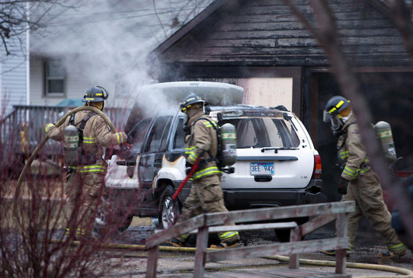 Firefighters with Aberdeen Fire and Rescue look over an automobile after putting out a fire Saturday afternoon at 321 N. Washington St.
