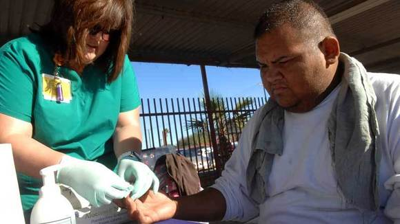 Christina Valencia (left), a nurse at El Centro Regional Medical Center, checks the blood sugar