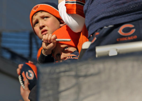 Chicago Bears' fans Korbe Hoover, 7, of Lynchfield, Ill. (bottom) and Andy Newcomb, 8, of Gurnee, Ill. wait for autographs before Bears play Minnesota Vikings at Soldier Field in Chicago on Sunday.