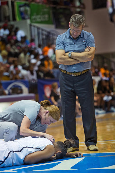 University of Connecticut's injured Kaleena Mosqueda-Lewis #23 is looked after by the team's trainer and Head Coach Geno Auriemma at the Paradise Jam women's college basketball tournament in St. Thomas, US Virgin Islands, Saturday.