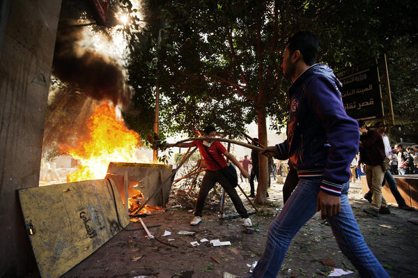 Protesters throw branches on a bone fire as they clash with Egyptian riot policemen at Simon Bolivar square on November 25, 2012 in Cairo. Egypt's powerful Muslim Brotherhood called nationwide demonstrations today in support of Islamist President Mohamed Morsi in his showdown with the judges over the path to a new constitution.