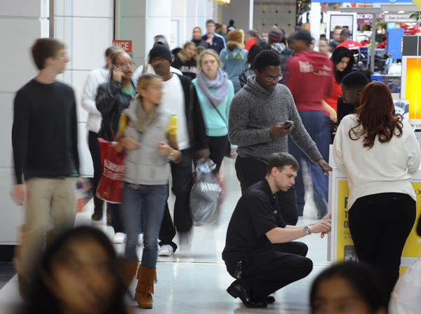 Kevin Jones, center, of Baltimore, is helped by salesman Mike Stender, center bottom, on a cell phone purchase as crowd of shoppers move around them at Towson Town Center on Black Friday.
