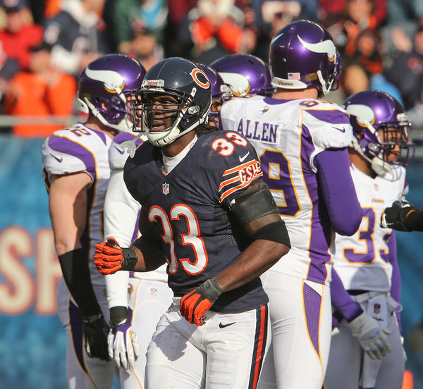 Cornerback Charles Tillman pumps his fist as he walks back to the bench after recovering the fumble by Vikings running back Adrian Peterson during the first half.