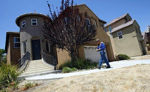 Temecula code enforcement officer Jean Voshall prepares to post a violation notice on this vacant house on Kingston Drive. Voshall is part of a team of inspectors who follow up on complaints of  code violations such as dead lawns, junk cars and algae-clogged swimming pools that incubate mosquitoes. The goal is  to help keep up neighborhood home values and the appearance of houses emptied because of the ongoing mortgage meltdown.