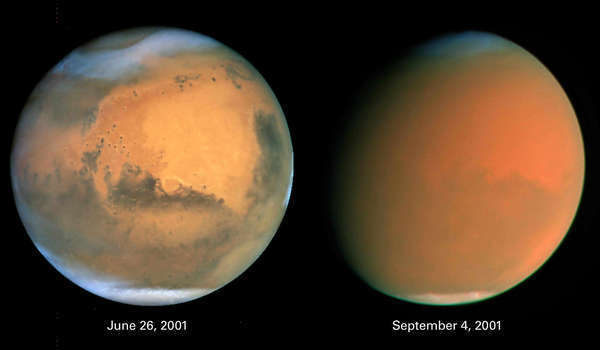 These images of Mars released by NASA in 2001 show a dust storm similar to one developing now. At left is the planet in natural color, as captured by the Hubble Space Telescope. The one on the right shows how a global dust storm engulfed Mars with the onset of Martian spring.