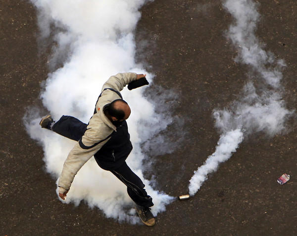 A protester tries to kick away a tear gas canister in Cairo.  More than 500 people have been injured in protests since Friday, after President Mursi's seizure of new powers sparked a political crisis.