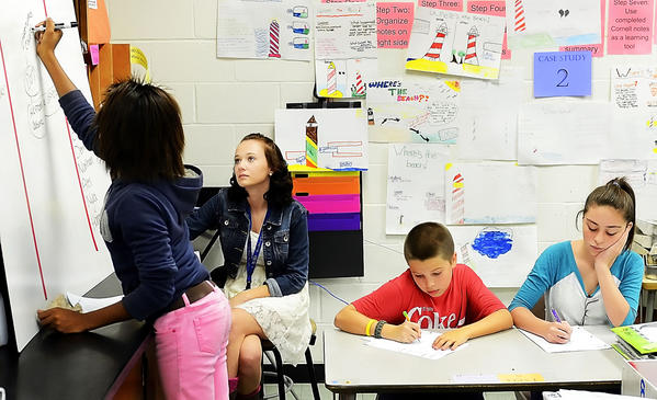 E. Russell Hicks Middle School seventh-grader Nyla Cummins, left, writes on a board as Hagerstown Community College student tutor Ashlee Renner watches and Alex Wright and Hannah Grace Frusher takes notes during an Advancement Via Individual Determination, or AVID class.