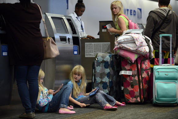Hunter Crosby, left, 9, and Scout Crosby, 8, play video games as they wait while their parents try to make alternative travel arrangements at San Francisco International Airport. Many flights to the East Coast were canceled due to Hurricane Sandy.