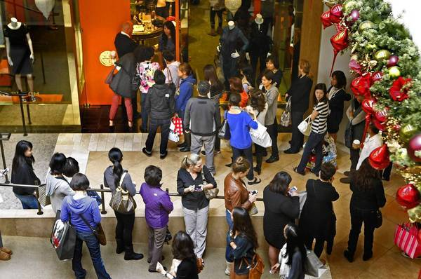 Spending per shopper jumped 6% to $423 over the long Black Friday weekend, according to the National Retail Federation. Above, shoppers line up Friday outside the Tory Burch women's clothing store in South Coast Plaza in Costa Mesa.