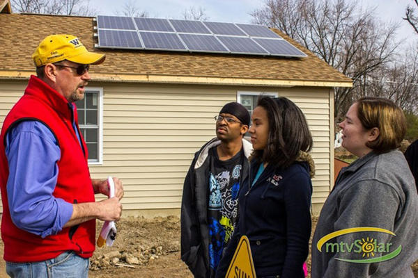 Explaining the solar panels on the roof of their new home to the Carr family are, from left, Colin Williams, vice president of Mountain View Solar in Berkeley Springs, W.Va., the company that installed the panels, and Wendell Carr, his daughter, Cierra Carr, 14, and wife, Tara Carr.