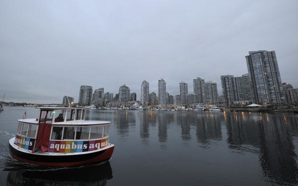 "An ""Aquabus"" water taxi ships in front of the Vancouver skyline ahead of the Winter Olympics on February 7, 2010.  Winter Olympics will be launched on February 12 with the opening ceremony at the ""BC Place Stadium."""